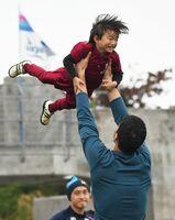 新加入のエドゥアルド選手は子どもを頭上に持ち上げて笑顔を誘った=沖縄県の読谷村陸上競技場