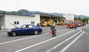 乗用車(左)を事故車両に見立てて、車線を規制する訓練をする消防隊員=佐賀市大和町の佐賀高速道路事務所