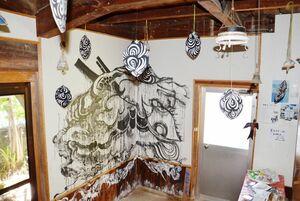 壁面に蜂の巣をイメージした墨絵やつり下がるオブジェ類