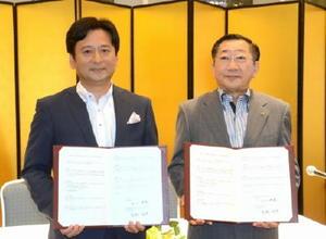 署名した連携協定書を手にする山口祥義知事とJR九州の青柳俊彦社長(右)=佐賀市のホテルニューオータニ佐賀