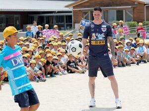 児童と一緒にリフティングするサガン鳥栖のフェルナンド・トーレス選手=鳥栖市