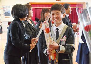 地域住民や職員から花を受け取り笑顔を見せる卒業生=佐賀市の嘉瀬小学校