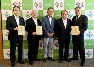 松本茂幸市長(右)らに冊子を贈る編集委員会の人たち=神埼市役所