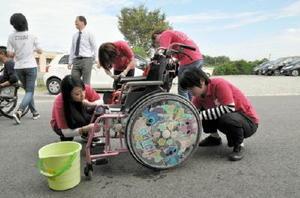 車いすを磨き上げる佐賀女子短大の学生たち=佐賀市の佐賀整肢学園オークス