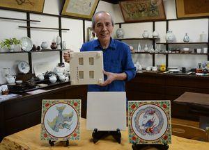 西本願寺の経蔵の陶板を再現した作品を手にする樋口憲人さん。手前中央も今回の再現品で、左右は以前の挑戦作品=有田町の乃利陶窯