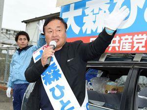 ドライバーに手を振りながら支持を訴える大森斉候補=唐津市のJR西唐津駅前
