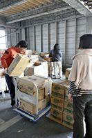 食器用洗剤などが入った箱を運ぶA-PADジャパンのスタッフら=佐賀市久保田支所内の倉庫