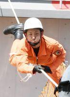 建物の間に水平に張られたロープ片道20メートルを往復する訓練「ロープブリッジ渡過」の様子=佐賀市の県消防学校