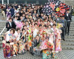 卒業した中学校の名前が書かれた旗を持って記念撮影する新成人たち=佐賀市文化会館