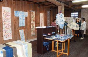 さまざまな色合いで染めたタペストリーや着物が並ぶ会場=嬉野市塩田町の杉光陶器店三の蔵「ギャラリー創」