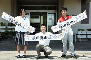 完成した濱田真由選手応援タオル。右がイラストを描いたOBの横尾丈一郎さん=佐賀市の高志館高校
