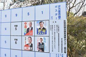 伊万里市議選のポスター掲示板の上に県議選の掲示板を重ねている=伊万里市