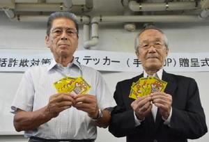 防犯ステッカーを受け取った民生委員の北村喜久夫さん(左)と中野勝文さん=佐賀市の諸富警察署