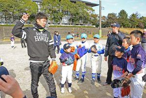 「腕を回して体全体で投げるといいよ」。岩嵜投手(左)からボールの投げ方を教わる参加者=唐津市相知町の天徳の丘運動公園