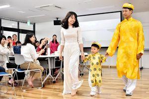 ファッションショーでベトナムの民族衣装「アオザイ」を紹介する留学生=佐賀市の佐賀メディカルセンタービル