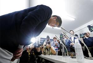 記者会見で謝罪するアパマンショップリーシング北海道の佐藤大生社長。手前右は消臭スプレー缶=18日夜、札幌市北区