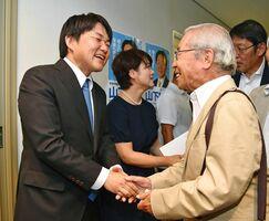 当選が確実となり、支援者と握手を交わす山下雄平氏(左)。中央は妻の華子さん=21日午後8時28分、佐賀市八幡小路の事務所