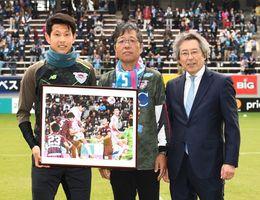月間MVPに選ばれたキム・ミンヒョク選手(左)に記念パネルを手渡した山口靖浩さん(中央)と佐賀新聞社の高井誠鳥栖支社長