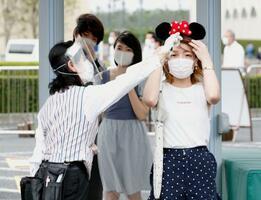 東京ディズニーランドで、入園前に検温する来園客(右)=1日午前7時16分、千葉県浦安市