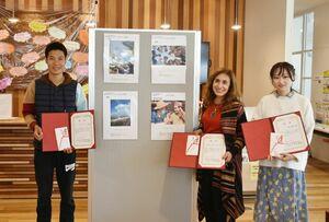 金賞を受賞したカルミナ・ルイズ・ムラカワさん(中央)と、銀賞を受賞したグエン・ディン・ソアンさん(左)、銅賞を受賞したコウ・テイシンさん=佐賀市の県国際交流プラザ
