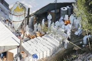 高病原性鳥インフルエンザが確認された養鶏場で作業する関係者=12日、香川県さぬき市(共同通信社ヘリから)