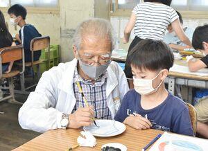 絵付け師の前田清次さん(左)に筆の使い方を教わる児童=伊万里市の大坪小