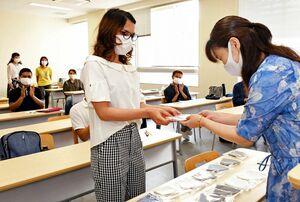 贈られた手作りマスクを受け取る西九州大短期大学部の留学生(左)=佐賀市の同大