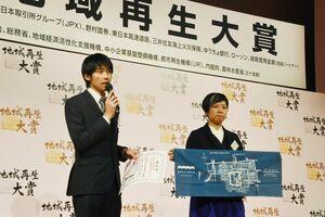 地域再生大賞ブロック賞に選ばれ、壇上であいさつをする川﨑会長(左)と滿原さん=東京・千代田区の都市センターホテル