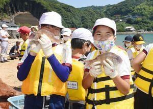 とれた魚を見せて喜ぶ児童たち=唐津市の幸多里の浜