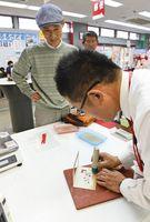 記念切手に「1.5.1」と記された日付印を押してもらう男性=佐賀市の中央郵便局