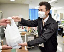 弁当を手渡す伊万里市社協の職員=同市松島町の事務所