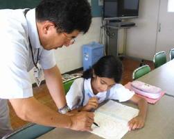 ネパール出身の女子児童に日本語を教える指導教員の西村常裕さん=佐賀市の本庄小