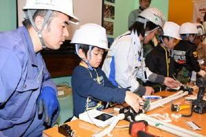 電気工事士の指導を受けながら、配線作業などに挑戦する子どもたち=佐賀市のメートプラザ佐賀