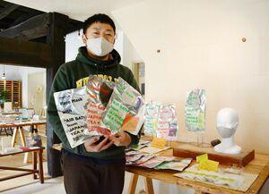 名尾和紙とうれしの茶で開発した防臭シートを入れたマスクを手にする谷口弦さん=佐賀市大和町の名尾手すき和紙ギャラリー
