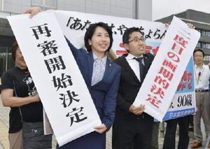 「大崎事件」で再審開始を認める決定が出され、鹿児島地裁前で垂れ幕を掲げる弁護士ら=28日午後