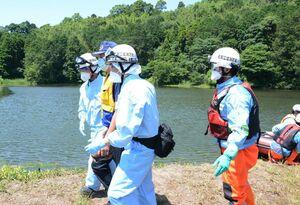 防護服を身につけ、新型コロナウイルスの感染疑いがある要救助者の対応をする消防隊員ら=神埼市神埼町尾崎の天神尾池