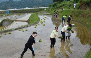 ぬかるむ棚田で田植えを楽しむオーナーの人たち=武雄市若木町