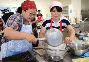 火にかけた牛乳に米酢を混ぜて分離させ、カッテージチーズとミルク酢(乳清)を作る参加者たち=佐賀市の西九州大学短期大学部