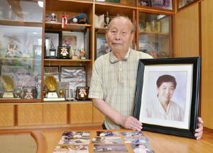 孝子さんの遺影を手に「現役でかなえられなかった日本一の夢をかなえてほしい」と話す義雄さん=鳥栖市の緒方新監督の実家
