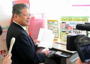 マイナンバーカードを利用し、戸籍証明書を取得した松本茂幸市長=神埼市のファミリーマート神埼日の隈店