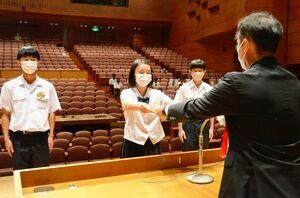 最優秀賞に輝き、表彰状を受け取る鳥栖商高の生徒=佐賀市文化会館