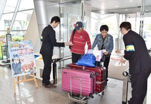 外国人旅行者にティッシュを配り、日本への肉の持ち込み禁止を呼び掛ける担当者=佐賀空港
