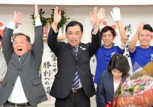 無投票で6選を果たし、万歳三唱する横尾俊彦氏(中央)と頭を下げる紀子夫人(右)=3日午後5時20分ごろ、多久市北多久町の事務所