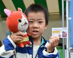 クイズに答え「子ども免許証」を受け取る来場者=佐賀市のアバンセ