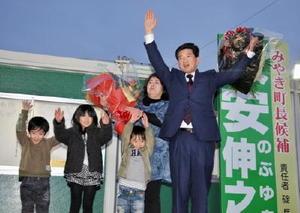 無投票での4選が決まり、花束を手に家族と笑顔を見せる末安伸之氏(右)=28日午後6時45分ごろ、みやき町原古賀の事務所前