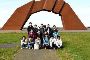 北方四島の返還を祈って造られた「四島のかけ橋」前で記念撮影する参加者=根室市納沙布岬