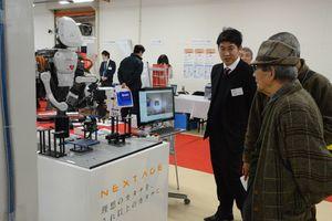 出展メーカーから産業用ロボットの説明を受ける来場者=佐賀市