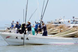 協力しながら海底に竹を突き刺す漁業者=佐賀県沖の有明海