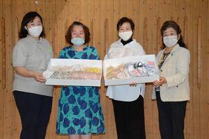 クレブスサポートの東内順子さん(右端)らからマスクを受け取る末次弘美所長(左端)=佐賀市の川原保育所