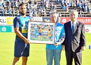 月間MVPに選ばれたオマリ選手に記念パネルを手渡した野口俊夫さんと佐賀新聞社の坂田勝次常務